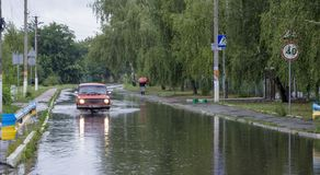 Czerwiec 21, Vyshenky Ukraina Konsekwencje prysznic Samochód bryzga przez wielkiej kałuży na zalewającej ulicie Obrazy Stock