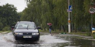 Czerwiec 21, Vyshenky Ukraina Konsekwencje prysznic Samochód bryzga przez wielkiej kałuży na zalewającej ulicie Zdjęcia Royalty Free