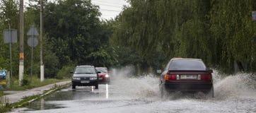 Czerwiec 21, Vyshenky Ukraina Konsekwencje prysznic Samochód bryzga przez wielkiej kałuży na zalewającej ulicie Zdjęcie Stock
