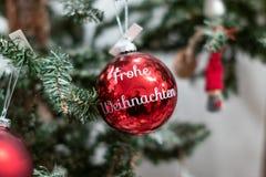 Czerwieni bożych narodzeń piłki z wrting «Frohe Weihnachten «na nim Weihnachtskugel mit Frohe Weihnachten obraz royalty free