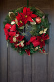 Czerwony Bożenarodzeniowy wianek na drewnianym drzwi Fotografia Stock
