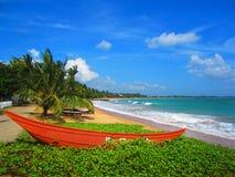 Czerwona łódź pod drzewkiem palmowym na piaskowatej plaży z dennymi falami obraz stock