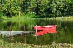 Czerwona łódź w jeziorze i odbiciu Obrazy Stock