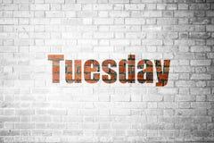 Czerwona ściana z cegieł tekstura z słowem Wtorek obraz stock