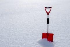 Czerwona śnieżna łopaty pozycja w śniegu Zdjęcia Stock