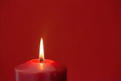 Czerwona świeczka pali jaskrawą Zdjęcie Royalty Free