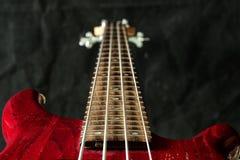 Czerwona basowa gitara z cztery sznurkami na ciemnym tle Obraz Stock