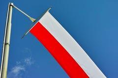 Czerwona biała flaga na słupie w niebie Obrazy Royalty Free