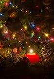 Czerwona Bożenarodzeniowa świeczka otaczająca sosnowymi gałąź zdjęcia royalty free