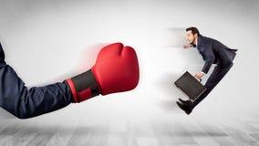 Czerwona bokserska rękawiczka puka out małego biznesmena fotografia stock