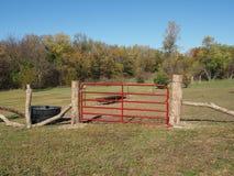 Czerwona brama obok fechtująca się w terenie fotografia stock