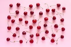 Czerwona dojrzała słodka wiśnia na różowym tle, teksturze lub tle, obrazy stock