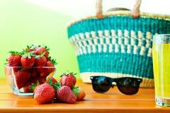 Czerwona dojrzała truskawka z zakupy koszem na stole Zdjęcia Stock