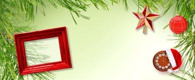 Czerwona drewniana rama z bożymi narodzeniami gra główna rolę, Święty Mikołaj kapelusz i zegar na zielonym tle, zdjęcia stock
