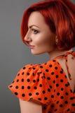 Czerwona dziewczyna w czerwonej sukni przy ścianą Zdjęcie Royalty Free