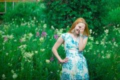Czerwona dziewczyny pozycja na kwiat łące fotografia royalty free