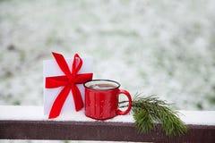 Czerwona filiżanka i list na śnieżnym moscie w zima parku Fotografia Royalty Free