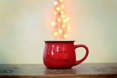 Czerwona filiżanka i serce kształtowaliśmy bokeh nad nim na białym tle Miłości kawy pojęcie fotografia royalty free