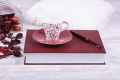 Czerwona filiżanka, książka i pióro na białym drewnianym tle, Zdjęcia Royalty Free
