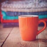 Czerwona filiżanka teaor kawa z stertą trykotowi pulowery obraz royalty free