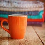 Czerwona filiżanka teaor kawa z stertą trykotowi pulowery na wo obraz stock