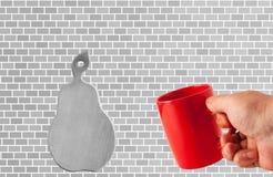 Czerwona filiżanka w ręce na ściany z cegieł tle obraz royalty free