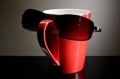 Czerwona filiżanka z okularami przeciwsłonecznymi Fotografia Stock