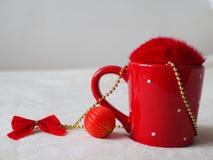 Czerwona filiżanka z puszystą pokrywą, bauble i łękiem, z bliska zdjęcia stock