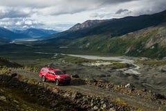 Czerwona furgonetka na wąskim śladzie nad gleczer dolina w Alaska Zdjęcia Royalty Free