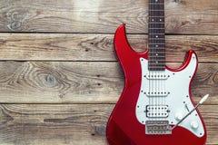 Czerwona gitara elektryczna na grunge desek drewnianym tle Miejsce fo zdjęcia stock