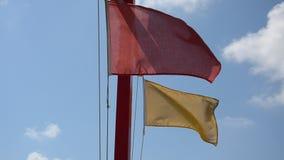 Czerwona i żółta flaga na plaży trzepocze w wiatrze