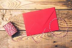 Czerwona i biali linowa czerwieni koperta na drewnianym stole i rolka Odgórny widok Zdjęcie Royalty Free