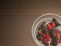 Czerwona i czarna morwa na drewnianym stole z zakończeniem w górę widoku Zdjęcie Royalty Free
