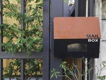 Czerwona i czarna stalowa skrzynka pocztowa przed stali ogrodzeniem z małym g Fotografia Stock