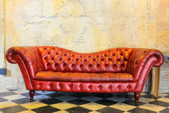 czerwona kanapa przy starą blick ścianą na W kratkę podłoga ilustracji