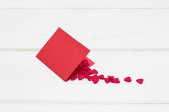 Czerwona kartka i few mali serca inside Zdjęcie Stock