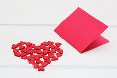 Czerwona kartka i few mali serca na białym drewnianym tle Zdjęcie Royalty Free