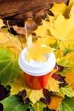 Czerwona kawa iść filiżanki witn marple liść na wierzchołku Spadku nastrój zdjęcia royalty free