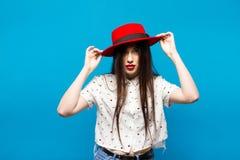 Czerwona kobieta czuł kapelusz Na błękitny tle Szczęśliwy i świeży Obrazy Stock