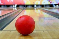 Czerwona kręgle piłka stawiająca na drewnianej alei z zamazaną kręgle szpilką Zdjęcie Stock