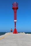 Czerwona latarnia morska na molu z mężczyzna obsiadaniem Zdjęcie Stock