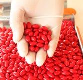 Czerwona medycyna w białej ręce Fotografia Royalty Free