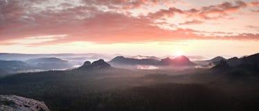 Czerwona mglista krajobrazowa panorama w górach Fantastyczny marzycielski wschód słońca na skalistych górach Mgłowa mglista dolin Zdjęcia Royalty Free