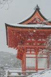 Czerwona pagoda przy Kiyomizu-dera świątynią z drzewem zakrywał białego śnieżnego tło Obraz Royalty Free