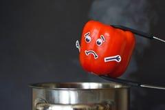 Czerwona papryka z smutnymi twarzy i gogle oczami stawia w parującego kucharstwo garnek na czarnym tle zdjęcia stock