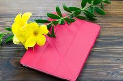 Czerwona pastylka z żółtymi florami na drewnianym tle Obrazy Stock