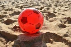 Czerwona piłka na piasku. Zdjęcia Royalty Free