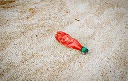 Czerwona plastikowa butelka rzucająca na plaży Zdjęcie Royalty Free