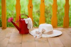 Czerwona polewaczka, ogrodowe rękawiczki i słomiany kapelusz, Fotografia Royalty Free