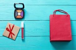 Czerwona pomadka, oko cienie, papierowa torba i prezenta pudełko na błękitnym drewnianym tle, Mod akcesoria Odgórny widok up i eg Zdjęcia Stock